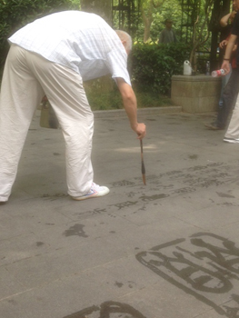Street art: Writing poetry with water in the park (Shanghai, China)